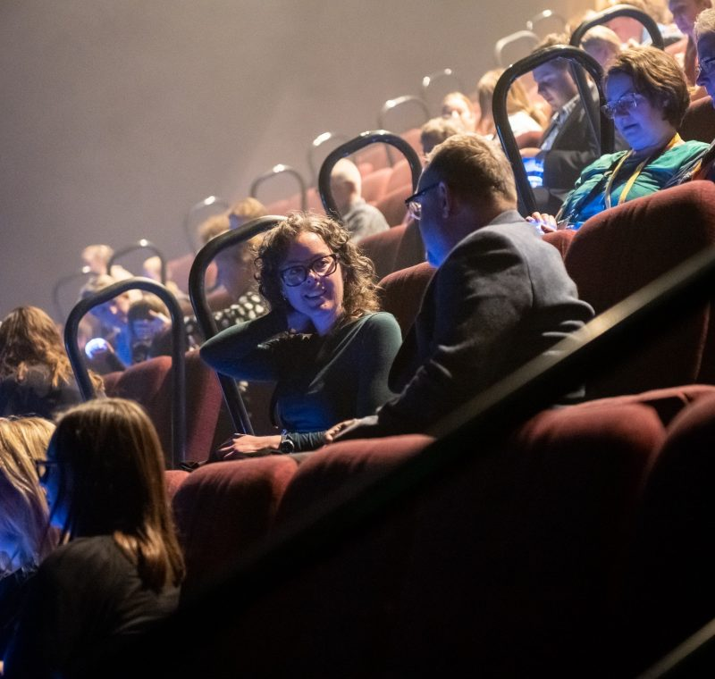 People sitting in an auditorium with dim lights, talking while waiting for a show to begin.